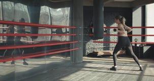 Mulher de Kickboxing nos airpods que treina o saco de perfuração no corpo feroz do ajuste da força do estúdio da aptidão video estoque