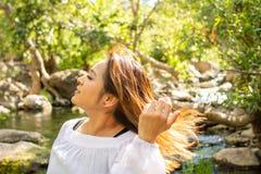 Mulher de Latina que joga seu cabelo para tr?s com seu cabelo no sol na frente das madeiras e um c?rrego na m?scara imagens de stock royalty free