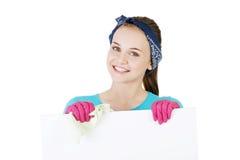 Mulher de limpeza feliz que mostra a placa vazia do sinal. foto de stock
