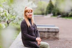 Mulher de meia idade bonita loura que senta-se no parque no fundo de florescer árvores de Apple imagens de stock royalty free