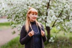 Mulher de meia idade bonita de sorriso loura no parque na primavera no fundo de florescer árvores de Apple imagem de stock royalty free