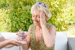 A mulher de meia idade com dor de cabeça, toma um comprimido Imagem de Stock