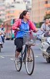 A mulher de meia idade dá um ciclo no centro da cidade, Kunming, China Foto de Stock