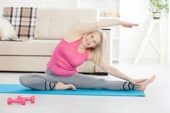 Mulher de meia idade em seu 50s que estica para o exercício Imagens de Stock Royalty Free