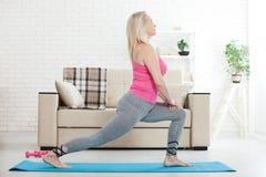 Mulher de meia idade em seu 50s que estica para o exercício Fotografia de Stock