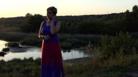 A mulher de meia idade está em um banco do lago e chama filme