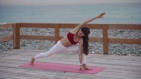 A mulher de meia idade faz a ioga na praia video estoque