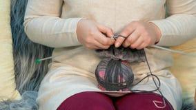 A mulher de meia idade faz malha a roupa de lã filme