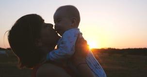 Mulher de meia idade feliz que beija um bebê em suas mãos no campo no por do sol imagem de stock royalty free