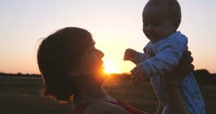 Mulher de meia idade feliz que beija um bebê em suas mãos no campo no por do sol no slo-mo filme
