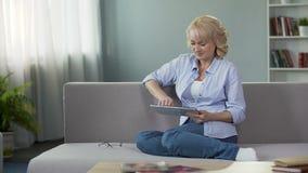 Mulher de meia idade feliz que vê vídeos engraçados na tabuleta, sentando-se no sofá em casa vídeos de arquivo