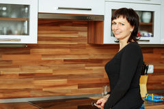 A mulher de meia idade limpa os pratos na cozinha Fotografia de Stock Royalty Free