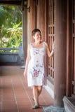 Mulher de meia idade moreno que anda abaixo do corredor com colunas de madeira Fotografia de Stock