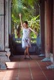 Mulher de meia idade moreno que anda abaixo do corredor com colunas de madeira Imagens de Stock