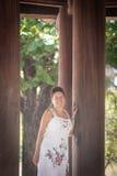 Mulher de meia idade moreno que anda abaixo do corredor com colunas de madeira Imagem de Stock