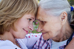 Mulher de meia idade que abraça sua mãe na natureza A emoção real fotografia de stock