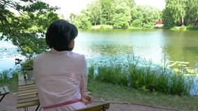 Mulher de meia idade que descansa perto da lagoa, sentando-se em uma tabela video estoque