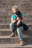 Mulher de meia idade que guarda o bassê em escadas Fotografia de Stock Royalty Free