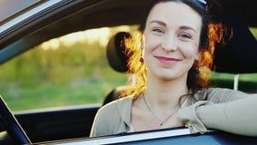 Mulher de meia idade que olha para fora a janela de um carro, sorrindo, retrato video estoque