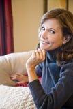 Mulher de meia idade que relaxa no sofá da sala de visitas fotografia de stock royalty free