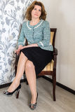 Mulher de meia idade que senta-se na cadeira na sala de visitas fotografia de stock royalty free