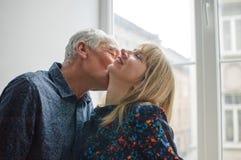 Mulher de meia idade quente e 'sexy' que aprecia o abra?o de seu marido idoso que est? perto da janela aberta dentro de sua casa  fotografia de stock royalty free