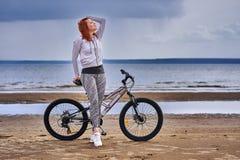 Mulher de meia idade ruivo no sportswear em uma caminhada da bicicleta na costa arenosa de um grande rio fotos de stock royalty free