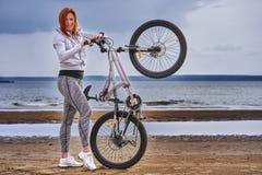 Mulher de meia idade ruivo no sportswear em uma caminhada da bicicleta na costa arenosa de um grande rio fotos de stock