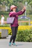 A mulher de meia idade toma o selfie em um parque, Pequim, China Imagens de Stock Royalty Free