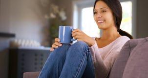 Mulher de Millenial que falam ao amigo na sala de visitas e assento de sorriso no sofá Imagens de Stock Royalty Free