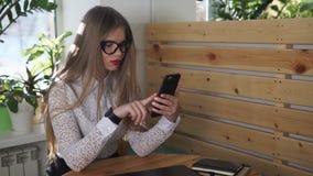 A mulher de negócio à moda verifica letras entrantes no telefone celular no caf filme
