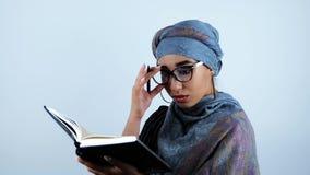 Mulher de negócio árabe bonita nova surpreendida tocando em monóculos após ter encontrado a informação necessária no caderno video estoque