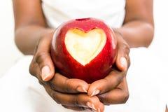 Mulher de negócio africana que guarda a maçã vermelha deliciosa com coração cortado fotos de stock royalty free