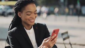 Mulher de negócio afro à moda que envia a mensagem audio da voz no telefone celular na fala exterior ao assistente móvel Neg?cios video estoque