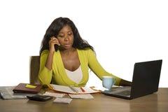 A mulher de negócio afro-americana preta atrativa e ocupada nova que trabalha em casa a mesa do computador de escritório que fala fotos de stock royalty free