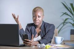 Mulher de negócio afro-americano desesperada e forçada nova que trabalha na mesa do laptop no problema do esforço do sofrimento d foto de stock