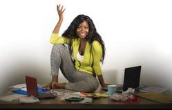 Mulher de negócio afro-americano feliz e atrativa nova que senta-se na mesa desarrumado do escritório completamente do sorriso do imagem de stock royalty free
