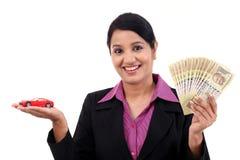 Mulher de negócio alegre com o carro do dinheiro e do brinquedo Fotografia de Stock