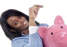 Mulher de negócio americana do africano negro que põe a moeda no piggybank cor-de-rosa desproporcionado fotografia de stock
