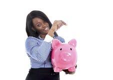 Mulher de negócio americana do africano negro que põe a moeda no piggybank cor-de-rosa enorme imagens de stock royalty free