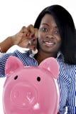 Mulher de negócio americana do africano negro que põe a moeda no piggybank cor-de-rosa enorme foto de stock royalty free