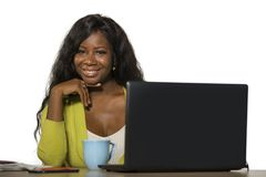 Mulher de negócio americana nova do africano negro feliz e atrativo que sorri trabalho alegre e seguro na mesa do computador de e imagem de stock royalty free
