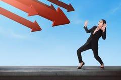 Mulher de negócio asiática chocada com a seta vermelha que vai para baixo a ela Fotografia de Stock Royalty Free