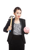 Mulher de negócio asiática com o banco e o martelo de moeda do porco Fotografia de Stock