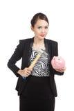 Mulher de negócio asiática com o banco e o martelo de moeda do porco Foto de Stock