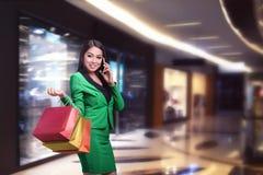 Mulher de negócio asiática com sacos de compras que fala no telefone Fotos de Stock Royalty Free