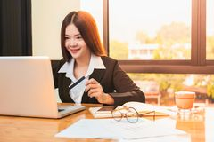 Mulher de negócio asiática feliz nova que guarda o cartão e a compra de crédito imagem de stock royalty free