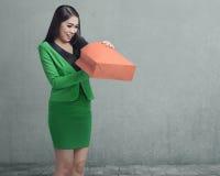 Mulher de negócio asiática feliz que abre seu saco de compras Fotos de Stock