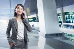 Mulher de negócio asiática feliz que fala em seu telefone celular fotos de stock royalty free