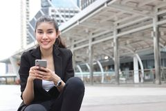 Mulher de negócio asiática nova alegre com o telefone esperto móvel no fundo urbano imagem de stock